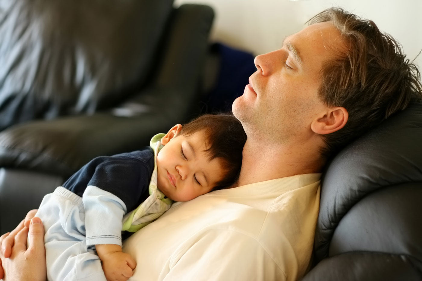 Father in recliner with baby sleeping