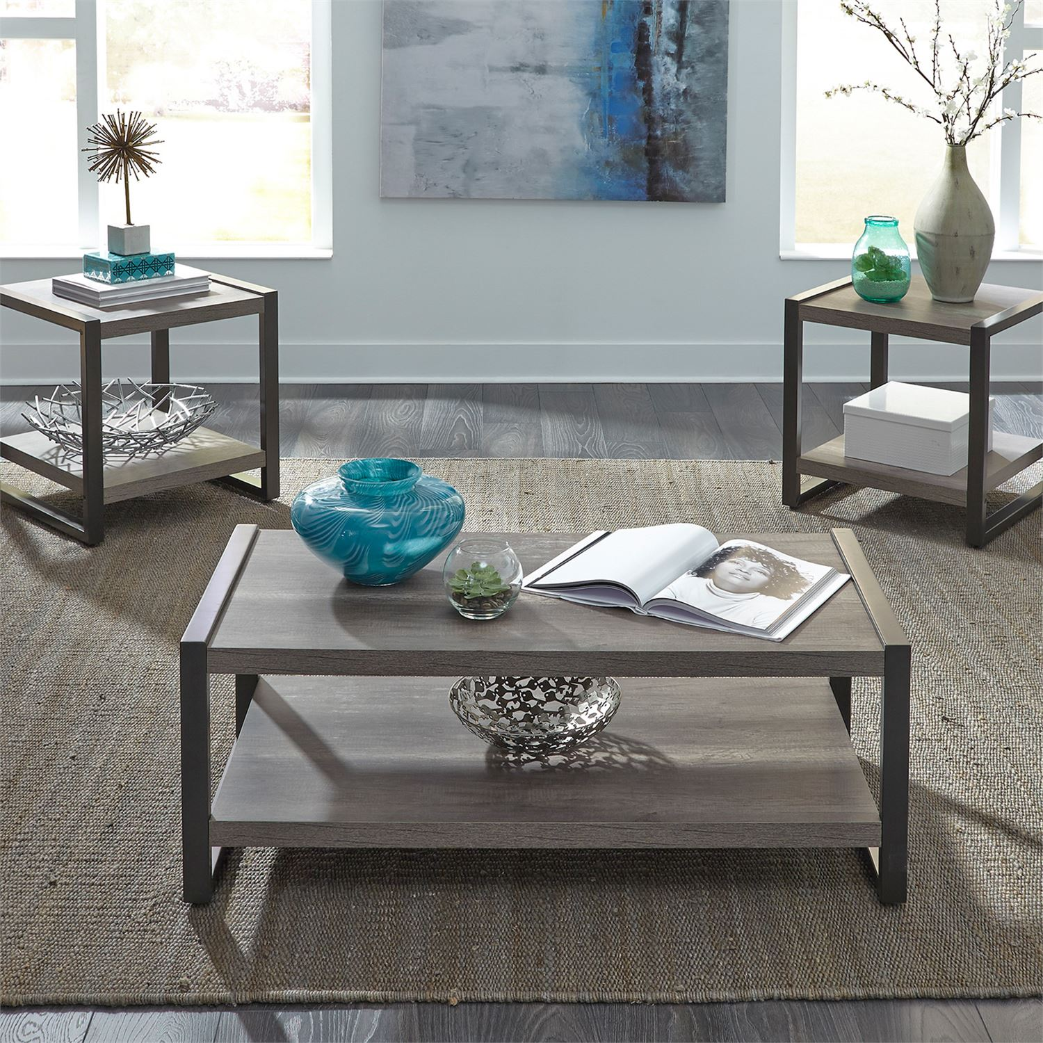 Three piece living room table set in a grey distressed coastal style