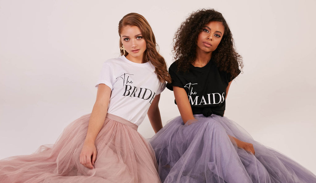"Two women modelling soft cotton tshirts with writing which says ""The Bride"" on one and ""The Maids"" on the other, wearing tutus."