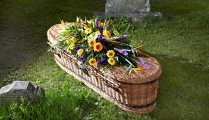 bright tropical flower casket spray on willow coffin