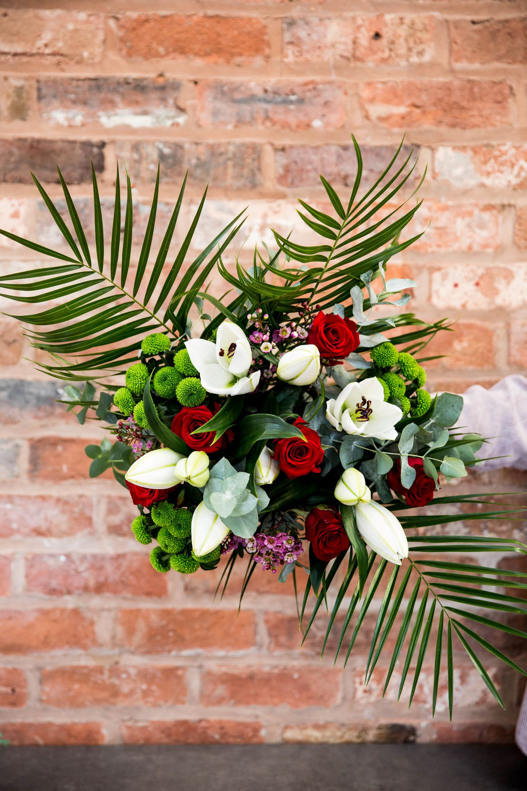 white lily, red rose, eucalyptus in a large hand tied bouquet