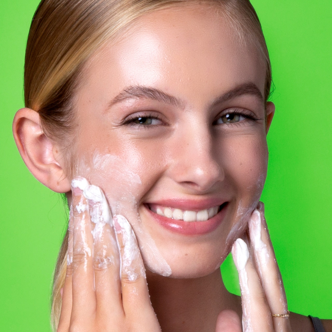 Girl scrubbing face with Clarify Cleansing Scrub