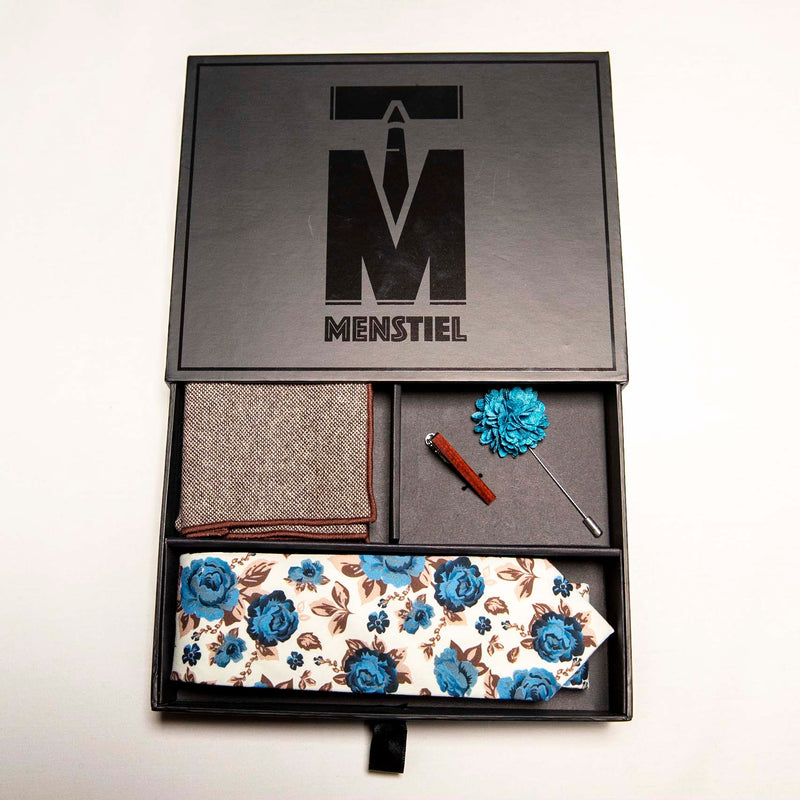 top view of chicory set in gift box with top - a men's accessories set - The earthy, wood tie bar along with the wool pocket square give rise to the bright, light blue flowers on the lapel pin and the floral tie