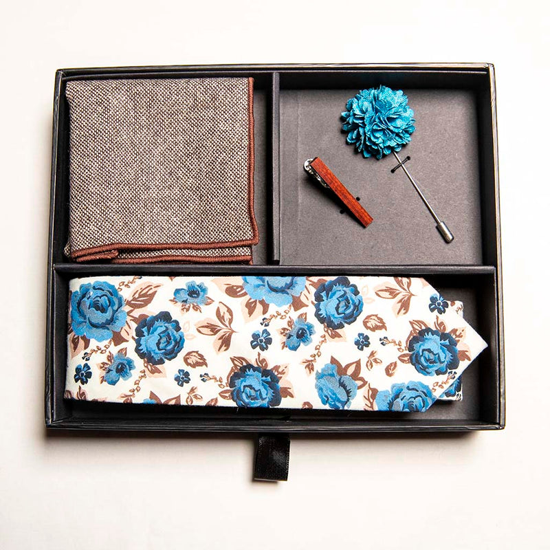 top view of chicory set in box - a men's accessories set - The earthy, wood tie bar along with the wool pocket square give rise to the bright, light blue flowers on the lapel pin and the floral tie