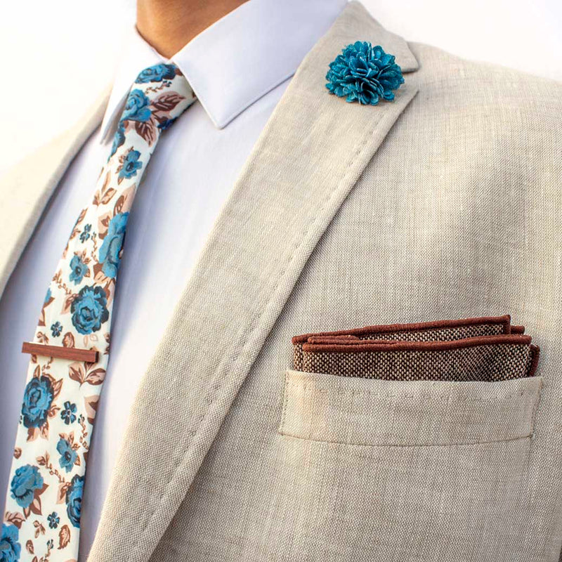 side angle of chicory men's accessories set on linen blazer -  The earthy, wood tie bar along with the wool pocket square give rise to the bright, light blue flowers on the lapel pin and the floral tie
