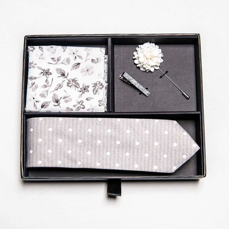 top view of menstiel's distorted set of men's suit accessories in gift box - A solid white lapel flower with a light floral design on the cotton pocket square is just a start. The grey cotton tie incorporates white polka dots over gray reverbs, and is held together by a fractured glass tie bar.