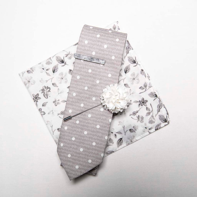 top view of menstiel's distorted set of men's suit accessories - A solid white lapel flower with a light floral design on the cotton pocket square is just a start. The grey cotton tie incorporates white polka dots over gray reverbs, and is held together by a fractured glass tie bar.