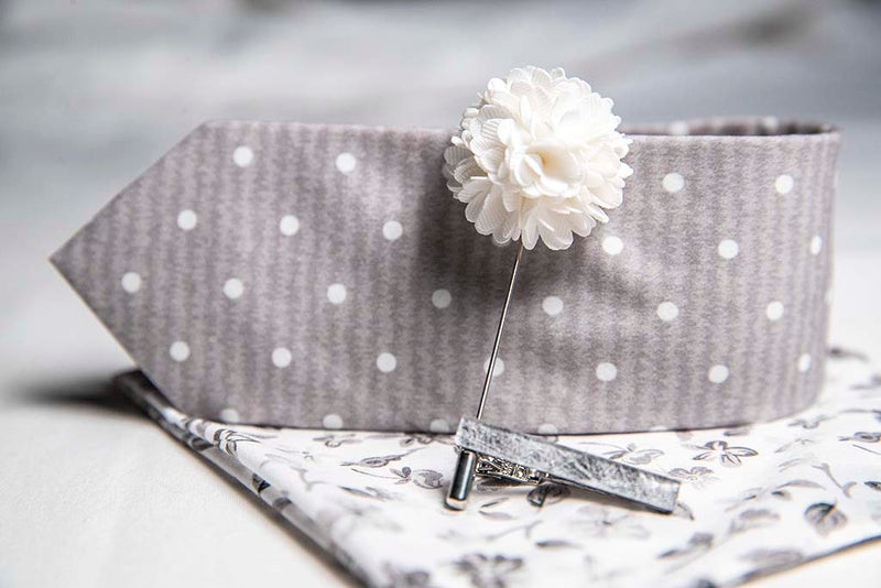 side view of menstiel's distorted set of men's suit accessories - A solid white lapel flower with a light floral design on the cotton pocket square is just a start. The grey cotton tie incorporates white polka dots over gray reverbs, and is held together by a fractured glass tie bar.