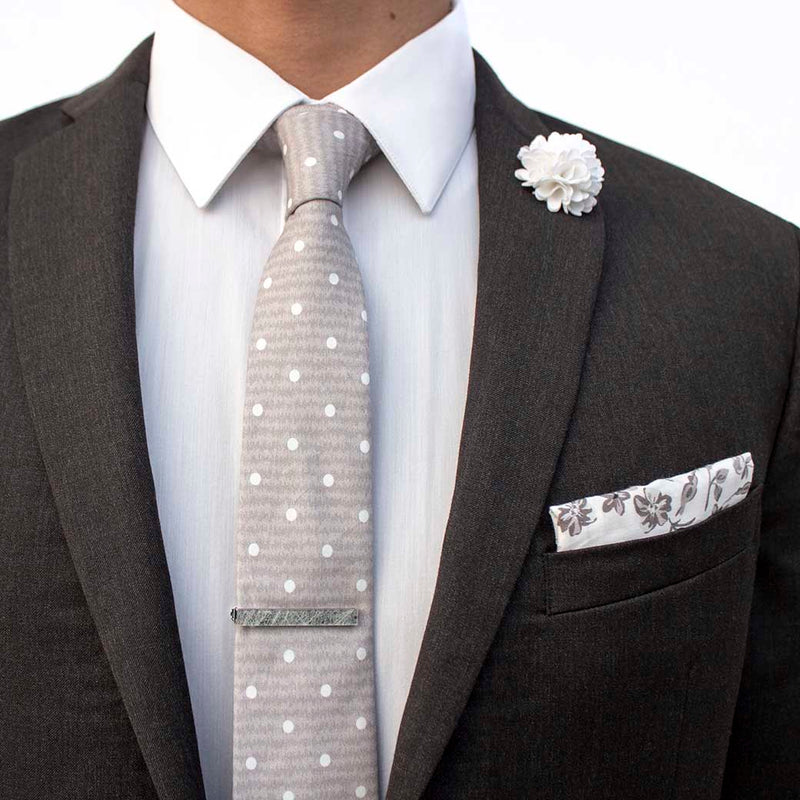 front angle of charcoal suit using menstiel's distorted set of men's suit accessories - A solid white lapel flower with a light floral design on the cotton pocket square is just a start. The grey cotton tie incorporates white polka dots over gray reverbs, and is held together by a fractured glass tie bar.