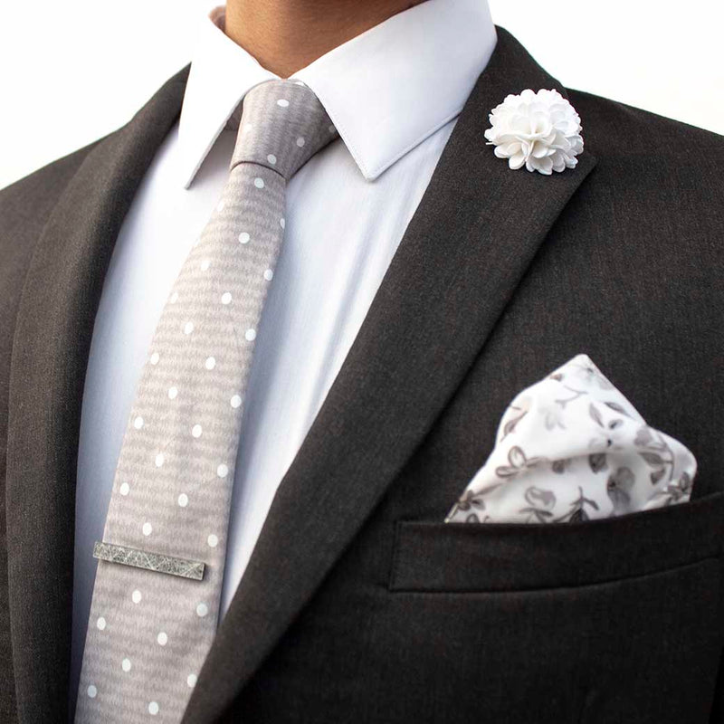 side angle of charcoal suit using menstiel's distorted set of men's suit accessories - A solid white lapel flower with a light floral design on the cotton pocket square is just a start. The grey cotton tie incorporates white polka dots over gray reverbs, and is held together by a fractured glass tie bar.