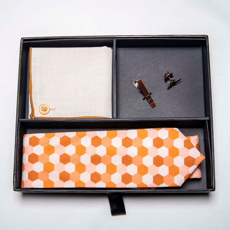 top view of honeycomb set of men's suit accessories in a gift box - A copper bee lapel pin along with a burnished tie bar highlight the multiple shades of rust on the hexagonal cotton tie. We added the double sided linen pocket square with an accentuated border and a sweet button as a finishing touch to the buzz