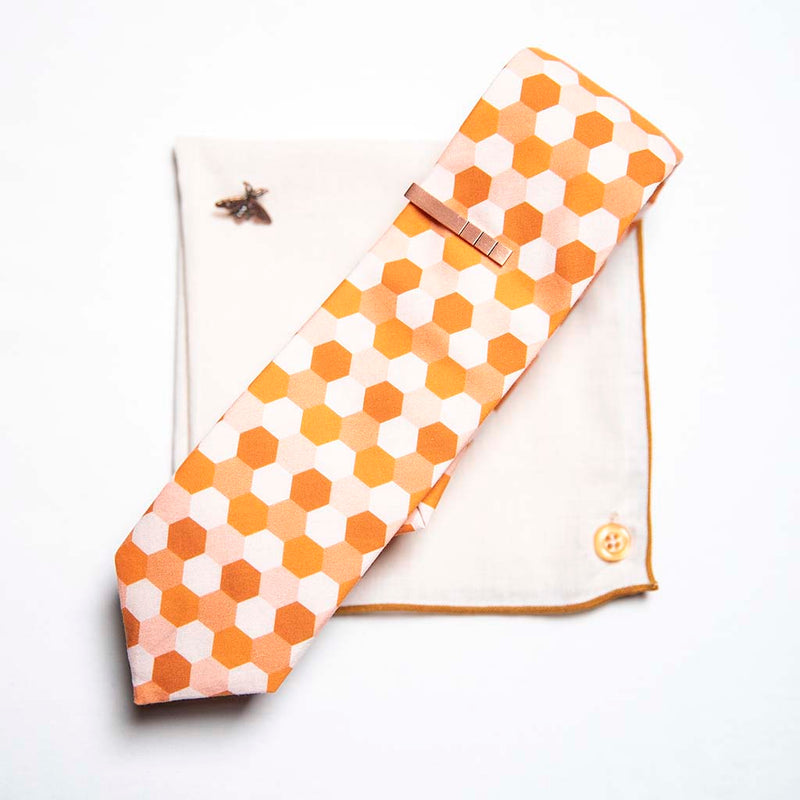 top view of honeycomb set of men's suit accessories - A copper bee lapel pin along with a burnished tie bar highlight the multiple shades of rust on the hexagonal cotton tie. We added the double sided linen pocket square with an accentuated border and a sweet button as a finishing touch to the buzz