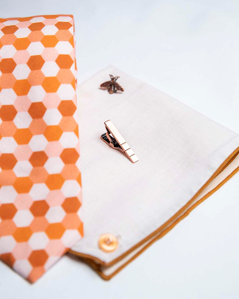 front view of honeycomb set of men's suit accessories - A copper bee lapel pin along with a burnished tie bar highlight the multiple shades of rust on the hexagonal cotton tie. We added the double sided linen pocket square with an accentuated border and a sweet button as a finishing touch to the buzz