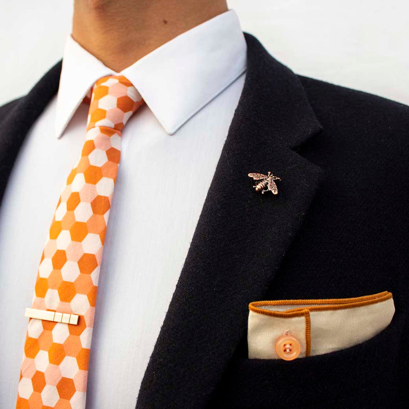 side angle of navy blazer using set of men's suit accessories - A copper bee lapel pin along with a burnished tie bar highlight the multiple shades of rust on the hexagonal cotton tie. We added the double sided linen pocket square with an accentuated border and a sweet button as a finishing touch to the buzz