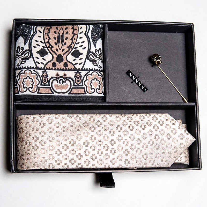 top view of pharaoh set of men's suit accessories in a gift box - he silk tie's simple pattern resembling hieroglyphics is a great contrast to the ornamental, paisley silk pocket square, and the black tie bar resembling a sarcophagus is the perfect complement to the gold skull lapel pin of the pharaoh himself