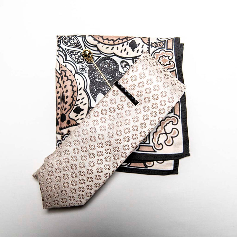 top view of pharaoh set of men's suit accessories - he silk tie's simple pattern resembling hieroglyphics is a great contrast to the ornamental, paisley silk pocket square, and the black tie bar resembling a sarcophagus is the perfect complement to the gold skull lapel pin of the pharaoh himself