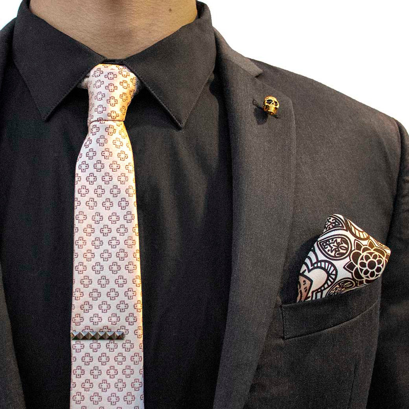 front angle of black charcoal suit with pharaoh set of men's suit accessories - he silk tie's simple pattern resembling hieroglyphics is a great contrast to the ornamental, paisley silk pocket square, and the black tie bar resembling a sarcophagus is the perfect complement to the gold skull lapel pin of the pharaoh himself
