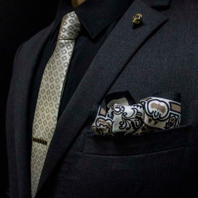 side angle of black charcoal suit with pharaoh set of men's suit accessories - he silk tie's simple pattern resembling hieroglyphics is a great contrast to the ornamental, paisley silk pocket square, and the black tie bar resembling a sarcophagus is the perfect complement to the gold skull lapel pin of the pharaoh himself