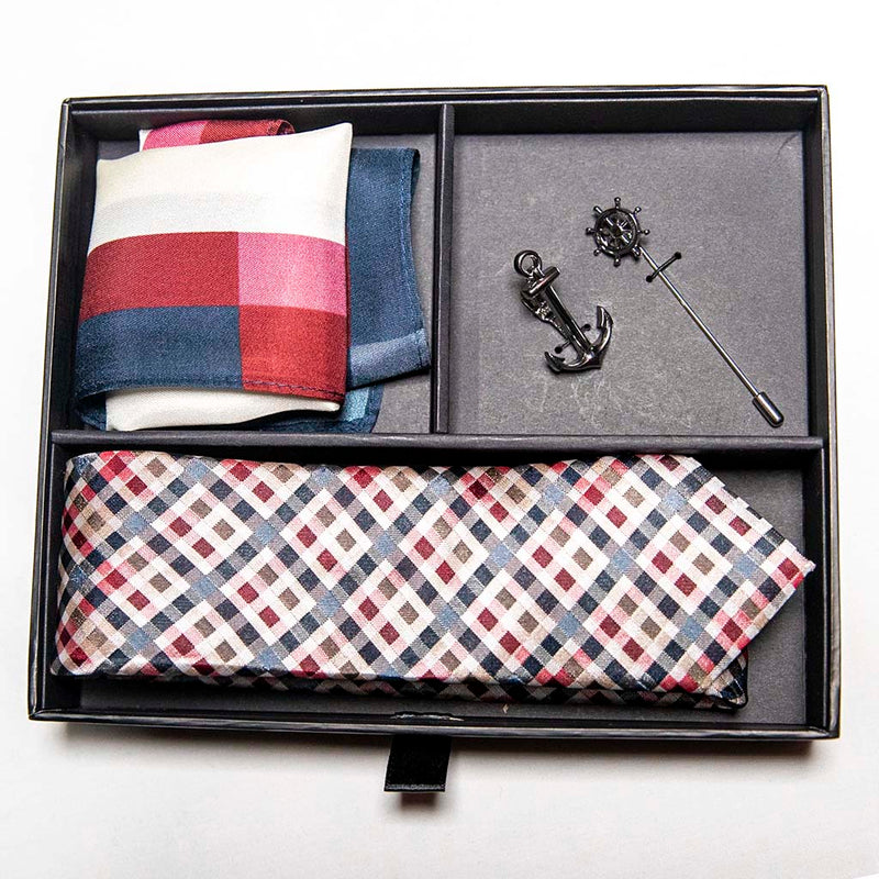 top view of voyage set of men's suit accessories in a gift box - The silver helm lapel pin on the breast represents choice, while the anchor tie bar on the chest symbolizes strength. These two coupled with the versatile, multi-colored silk tie and silk pocket square make a great combination