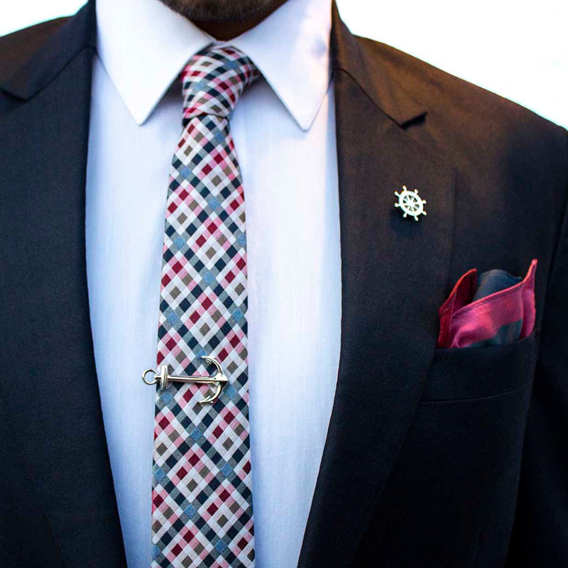 front angle of navy suit using voyage set of men's suit accessories - The silver helm lapel pin on the breast represents choice, while the anchor tie bar on the chest symbolizes strength. These two coupled with the versatile, multi-colored silk tie and silk pocket square make a great combination