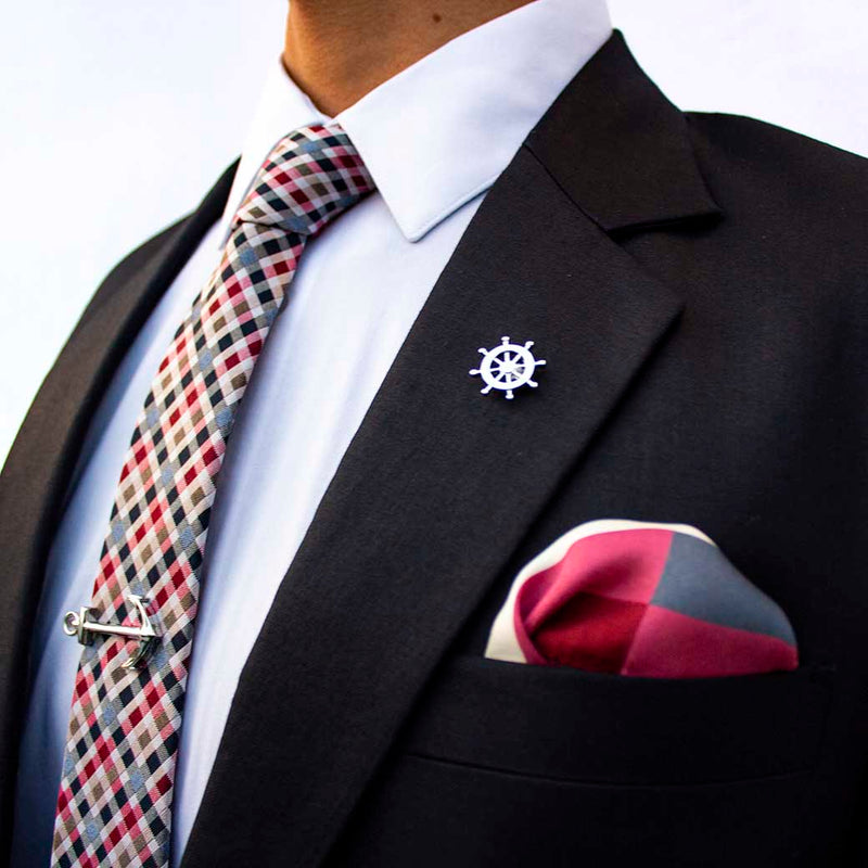 side angle of navy suit using voyage set of men's suit accessories - The silver helm lapel pin on the breast represents choice, while the anchor tie bar on the chest symbolizes strength. These two coupled with the versatile, multi-colored silk tie and silk pocket square make a great combination