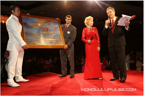 Eva Makk helping auction off her painting at the American Heart Association Heart Ball