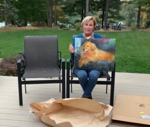 Photo of lady holding a surprise portrait painting of her golden retriever Simon.