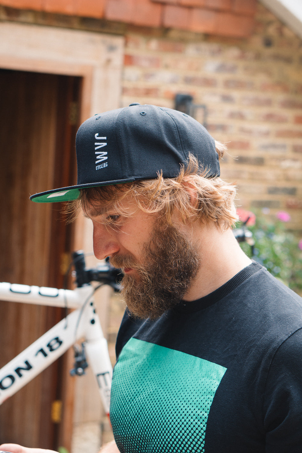 Jam Snapback cap showcasing green base stitched Jam logo symbol worn by JAM CEO fixing a bike