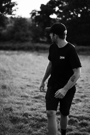 Francis Cade walking in a park looking into the distance wearing the new black CADE t-shirt with white logo