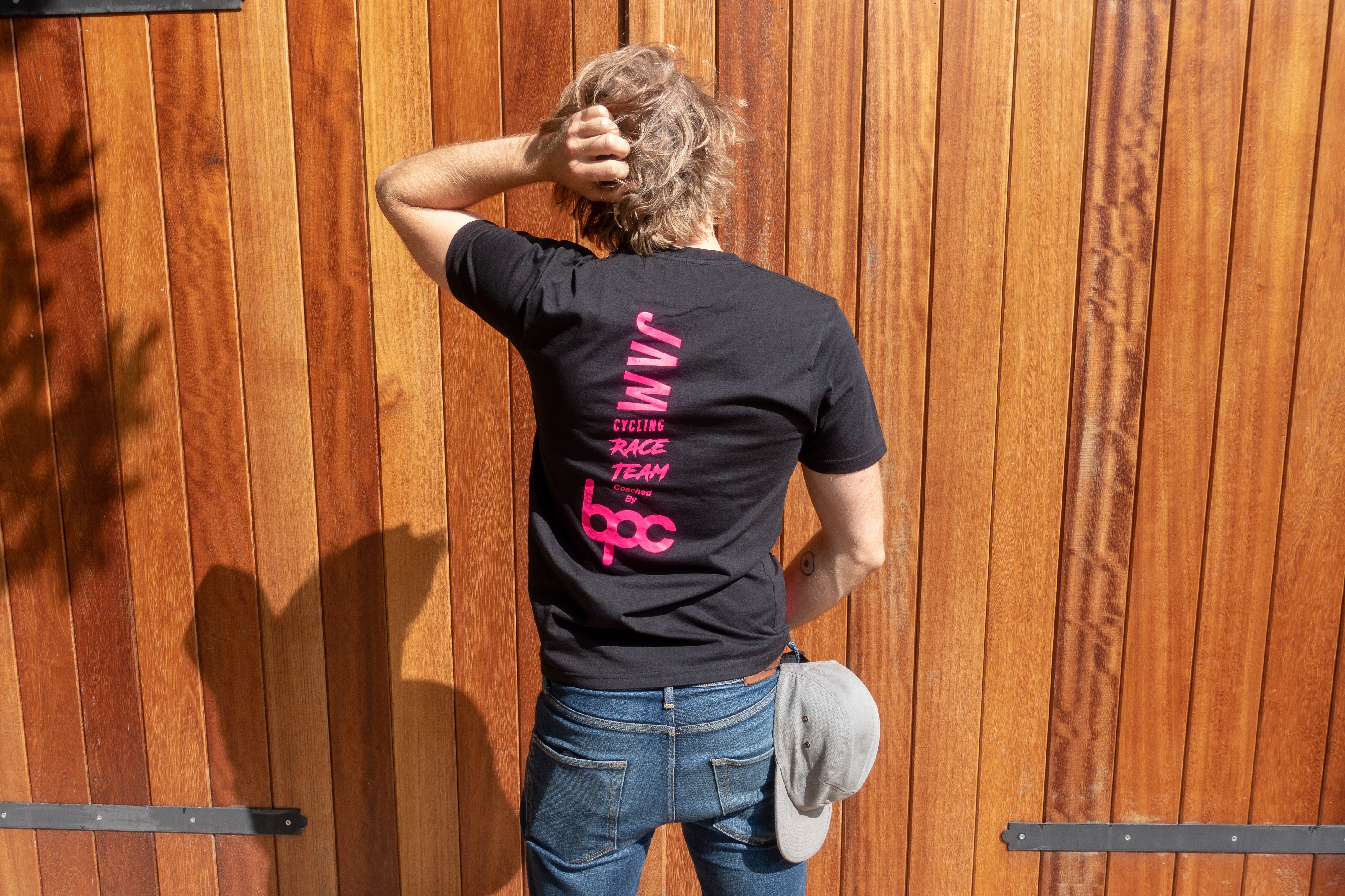 Black JAM Race team t-shirt featuring HOT logos  worn by Jam CEO with blue jeans and brown beltagainst barn door
