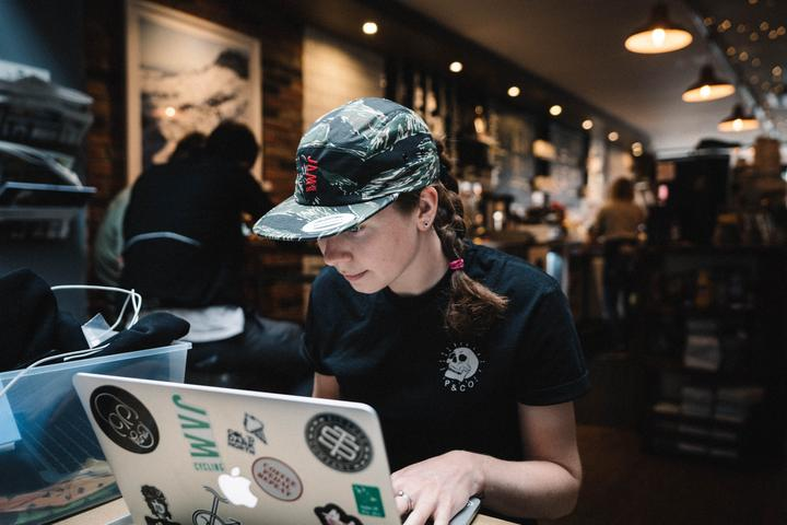 Jamouflage 5 panel cap showcasing HOT PINK am logo symbol worn by JAM female employee Jess sitting working at laptop in a cafe
