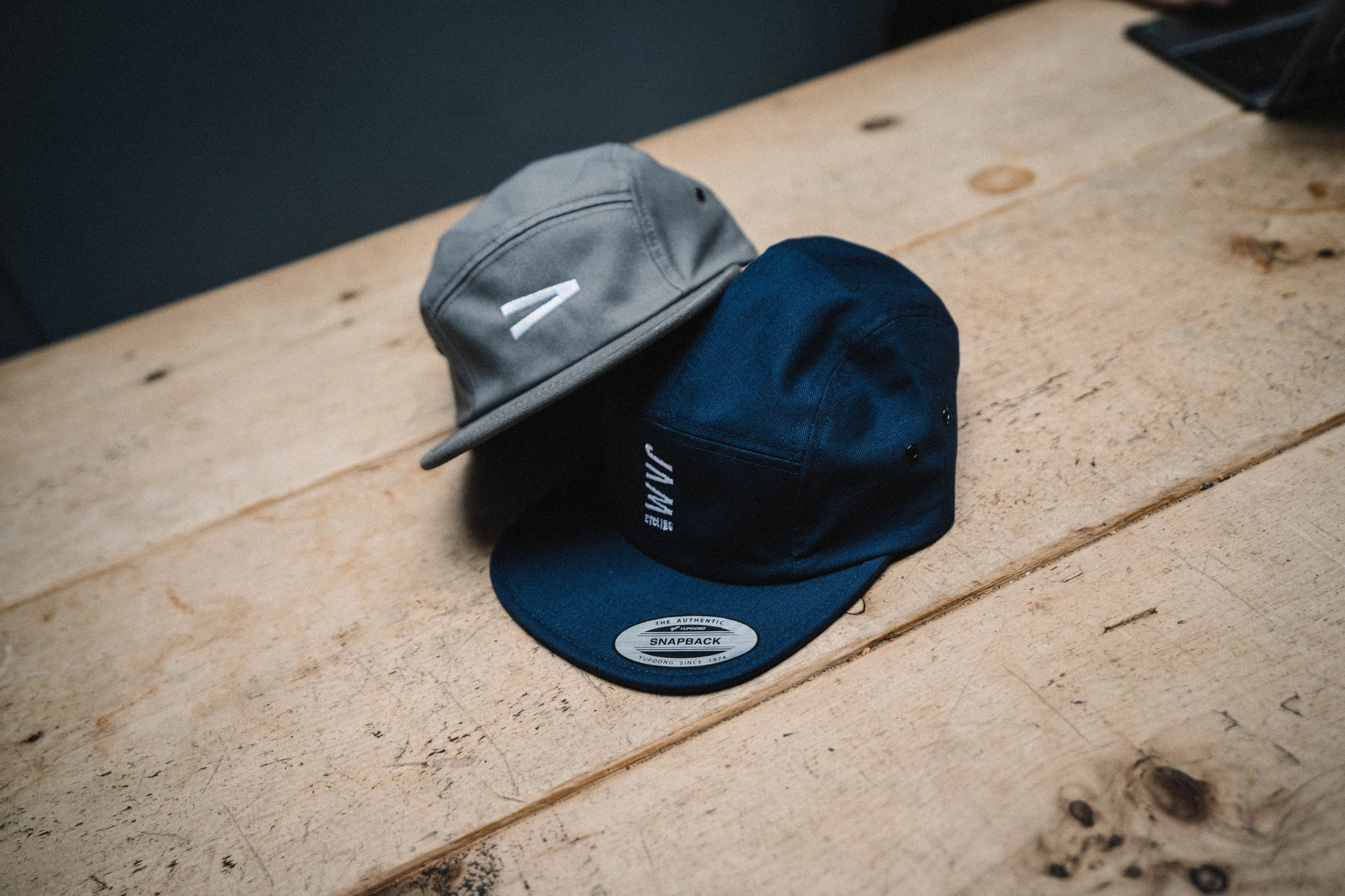 Navy and Grey JAM caps sitting together on a light wooden desk