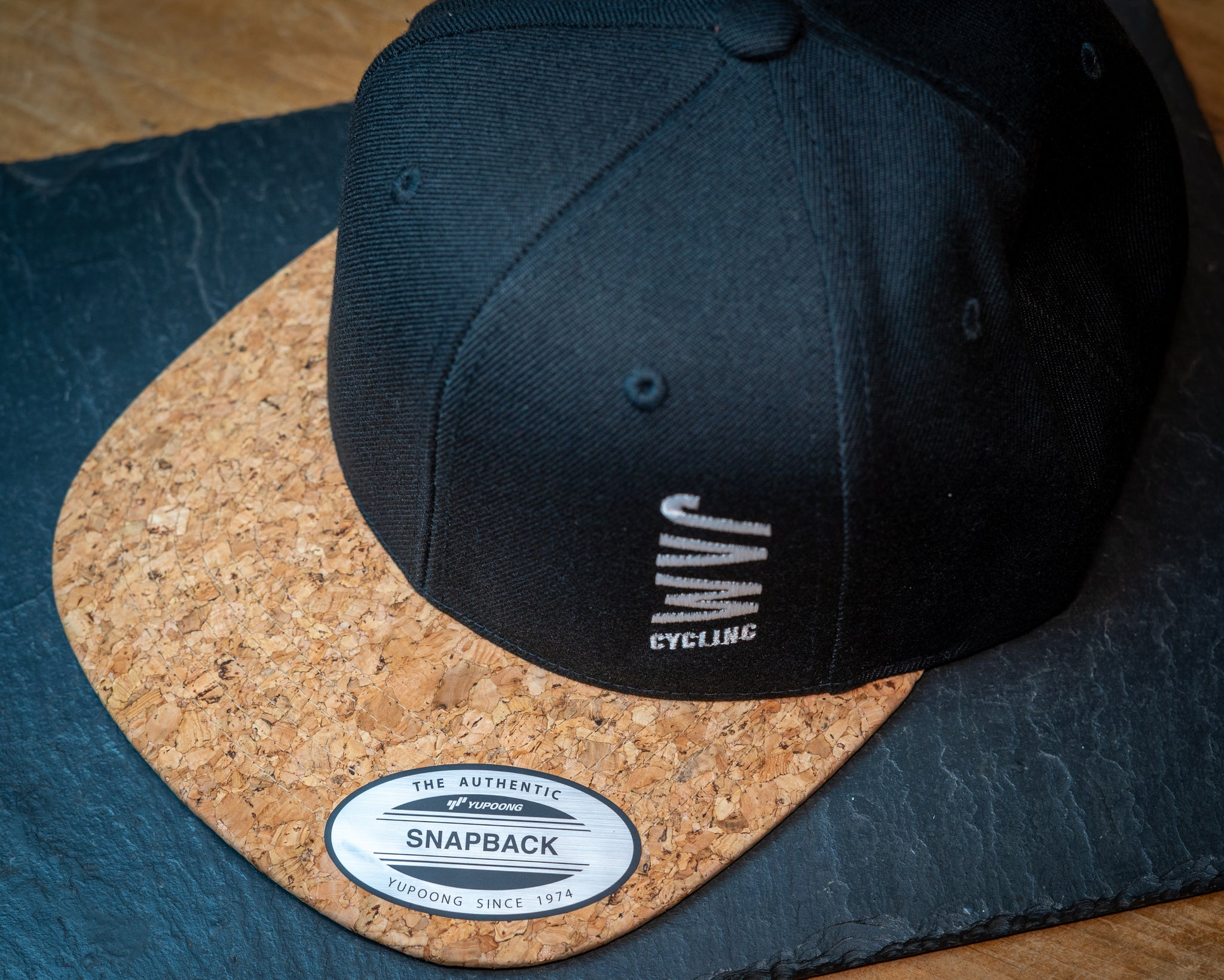 JAM snap back cap featuring cork peak stitched JAM logo up close detail on a black slate background cool product photography