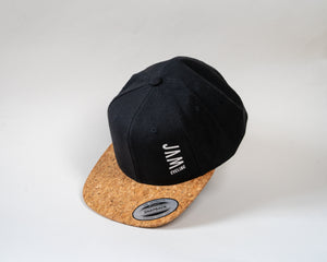 JAM snap back cap featuring cork peak stitched JAM logo floating on a white background cool product photography