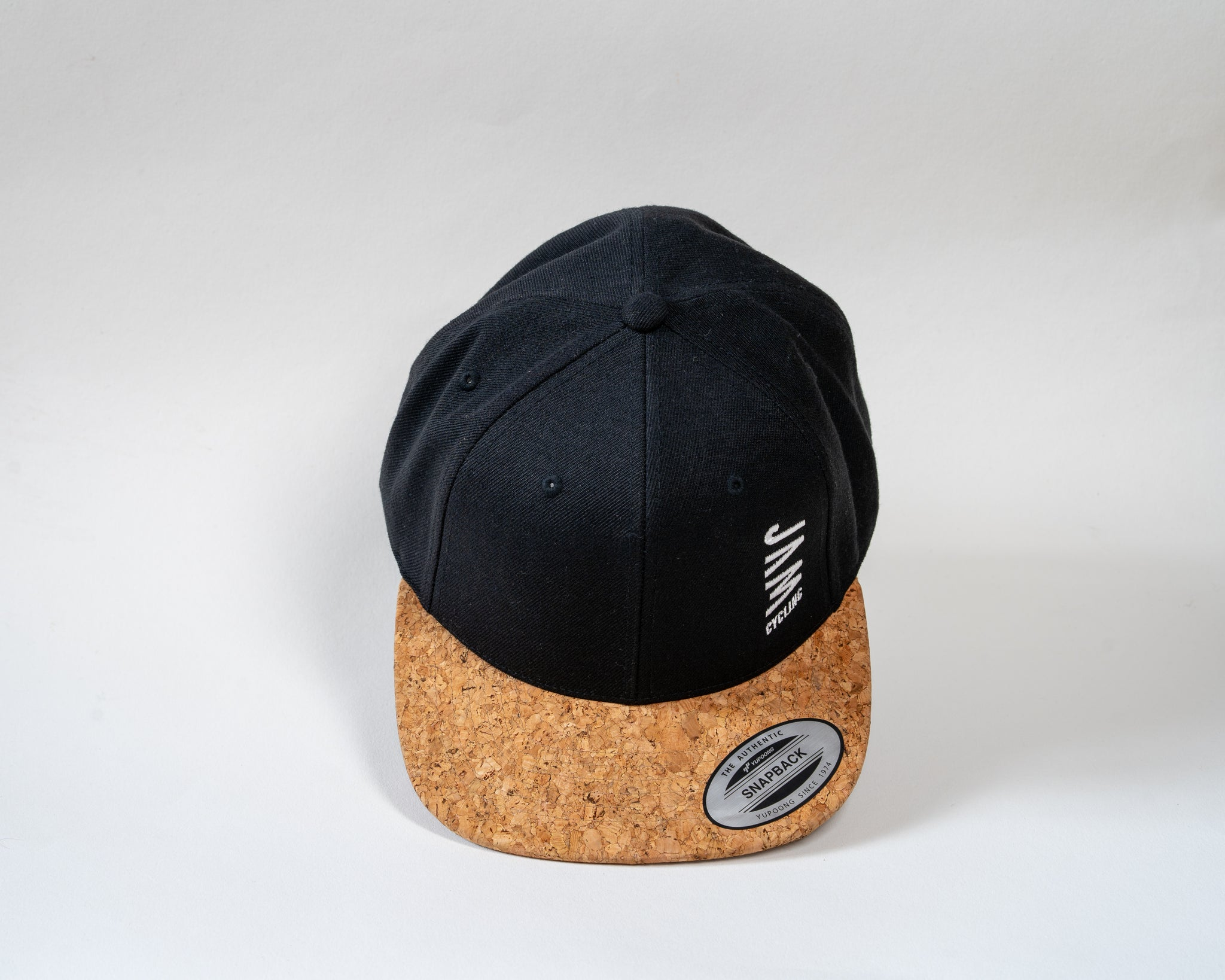 JAM snap back cap featuring cork peak stitched JAM logo floating on a white background