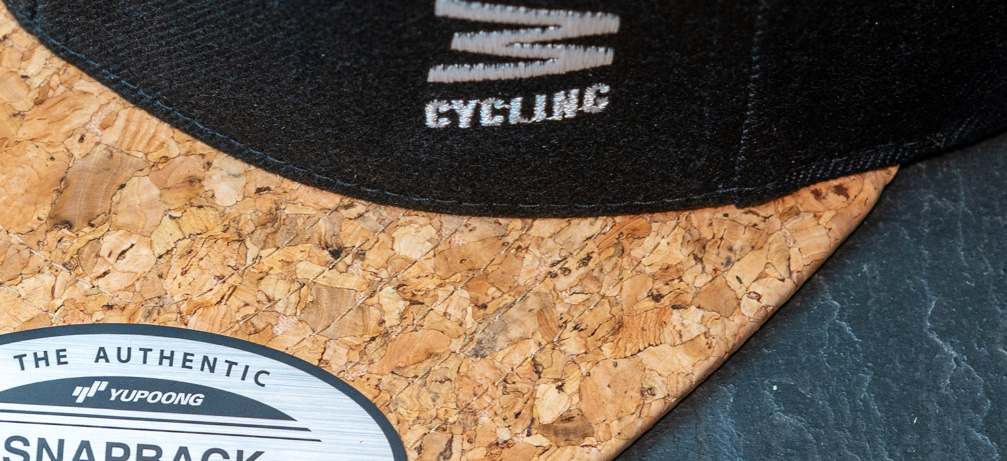 JAM snap back cap featuring cork peak stitched JAM logo up close detail on a black slate background