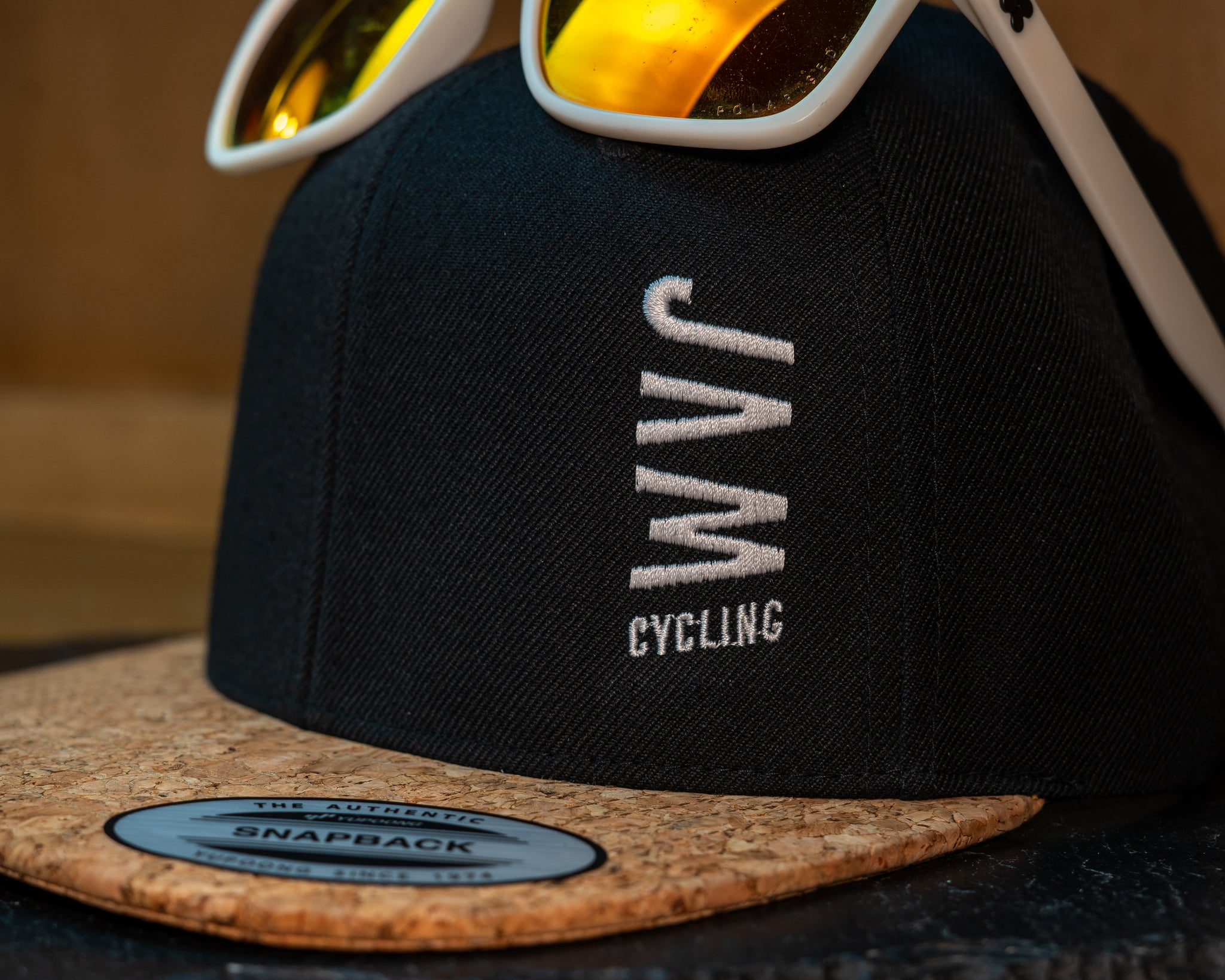 JAM snap back cap featuring sunglasses cork peak stitched JAM logo up close detail on a black slate background cool product photography
