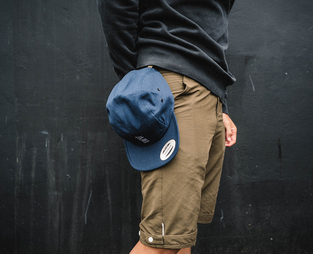 Navy 5 panel cap hanging from the belt of a Jam employee