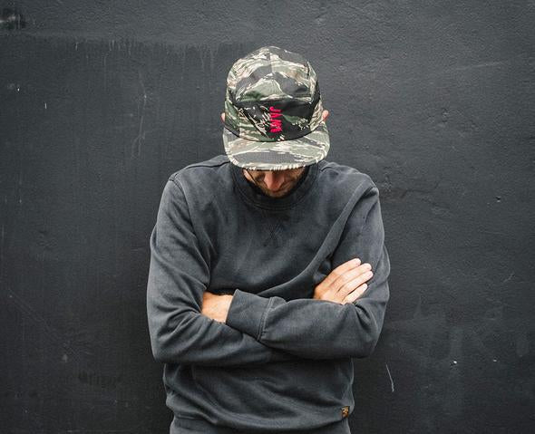 Jamouflage 5 panel cap showcasing HOT PINK am logo symbol worn by JAM employee Francis CADE against a black wall
