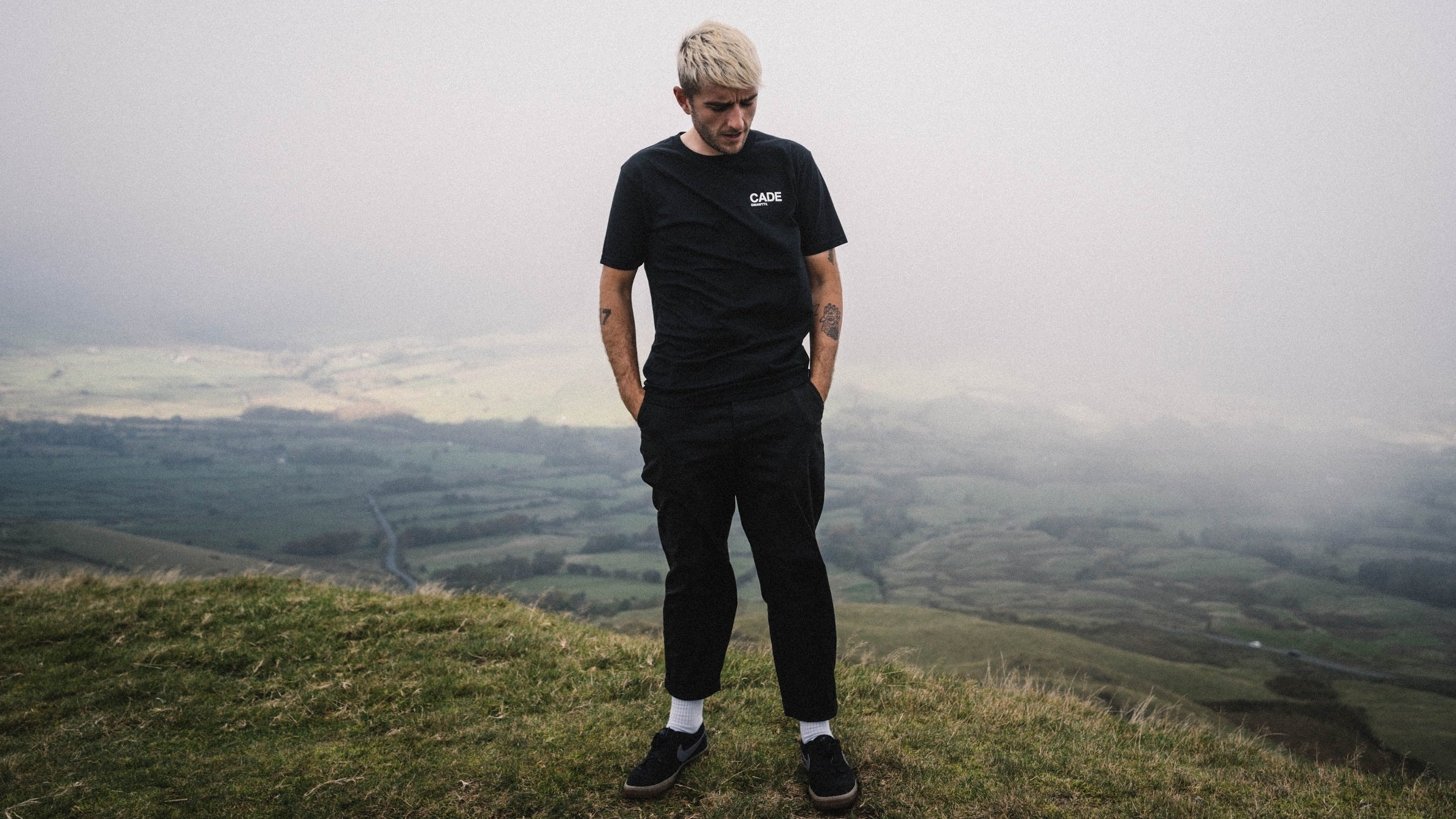 Francis Cade stood on a hill in the PEAK district looking into the distance wearing the new CADE t-shirt