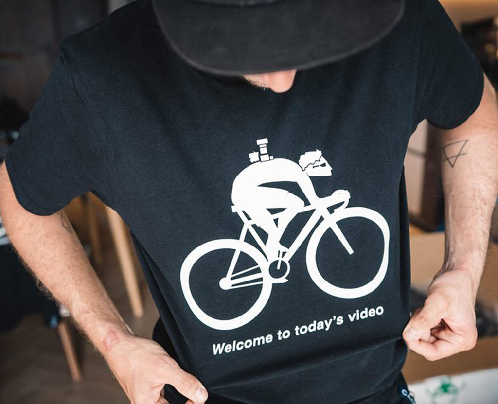 "T-shirt showing cartoon cyclist with camera on his back saying ""Welcome to todays video"" by Francis CADE"