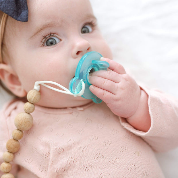 Baby girl wearing pacifier clip