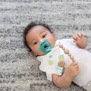 Baby with pacifier in mouth and clip on bib