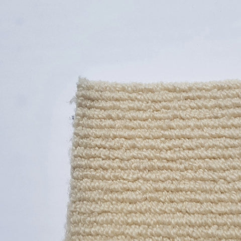 Corner of cheap Cream wool carpet tile with a high low loop pattern