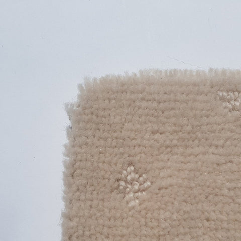corner of a carpet roll in cream, stocked at cheap carpet melbourne australia made of wool and loop and plush combination fibres.