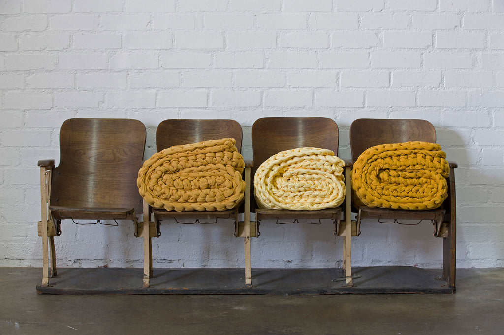 mustard french terry banana taffy and vintage gold weighted blankets on chairs