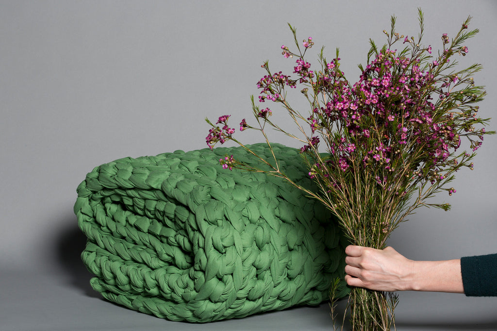 green clover weighted blanket folded with hand holding flowers