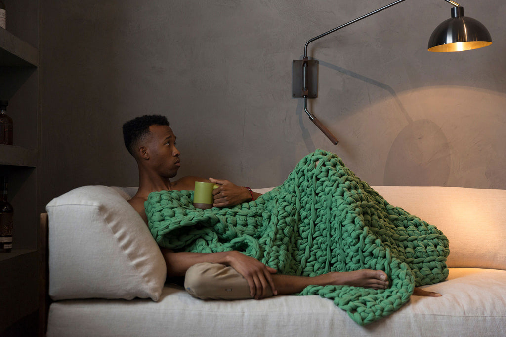 person on couch with green clover weighted blanket and green mug