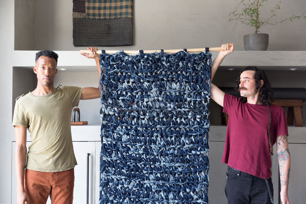 two men holding up denim weighted blanket hanging from wooden stick