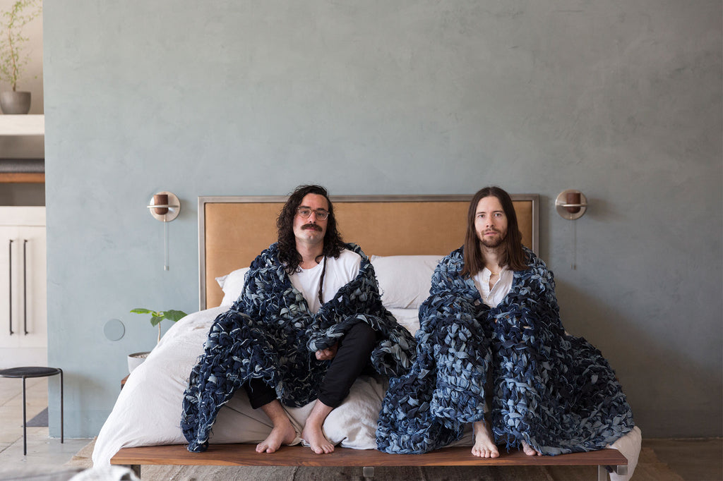 two men sitting on bed with denim weighted blankets draped over shoulders